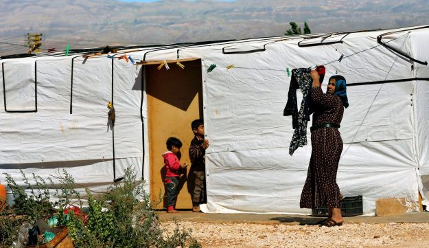In this June 20, 2017 file photo, a Syrian refugee hangs laundry outside her tent at a Syrian refugee camp in the eastern city of Baalbek, Lebanon.