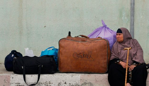 A Palestinian woman waits near her belongings before crossing into Egypt through the Rafah border crossing, southern Gaza Strip, Thursday, May 26, 2011