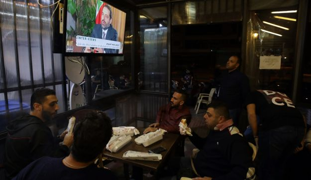 """Lebanese watch an interview with Lebanon's resigned prime minister Saad Hariri at a coffee shop in Beirut on November 12, 2017. Saad Hariri pledged he would return to Lebanon from Saudi Arabia """"very soon,"""" in his first television interview since his shock resignation as prime minister eight days ago. / AFP PHOTO / ANWAR AMRO"""