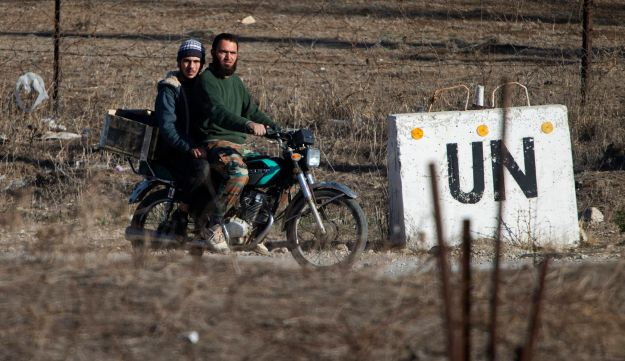 Two men, not specified which group of rebels, ride a motorcycle towards an abandoned UN base at Syria's Quneitra border crossing between Syria and the Israeli-controlled Golan Heights, Monday, Nov. 28, 2016. The Israeli military says it has carried out an air strike in Syria on a building used by Islamic State militants to attack Israeli forces. The overnight air strike Monday targeted an abandoned United Nations building that Israel says was used as a base by the militants. (AP Photo/Ariel Schalit)