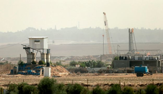A picture taken from the eastern outskirts of Gaza Strip shows an Israeli drilling machine stationed on the Israeli side of the border on November 12, 2017. / AFP PHOTO / MAHMUD HAMS