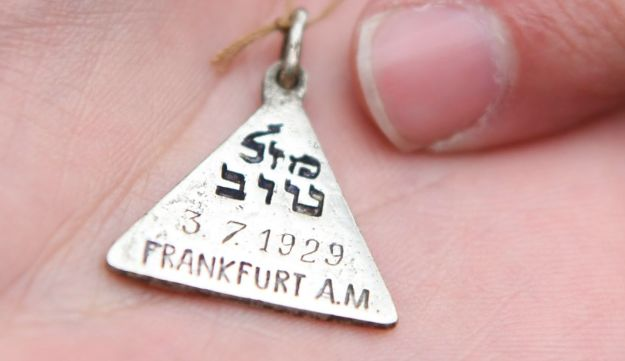 Greg Schneider, Executive Vice President of the Jewish Claims Conference, presenting a replica of Karolina Cohn's pendant during the ceremony, Frankfurt, Germany, November 13, 2017.