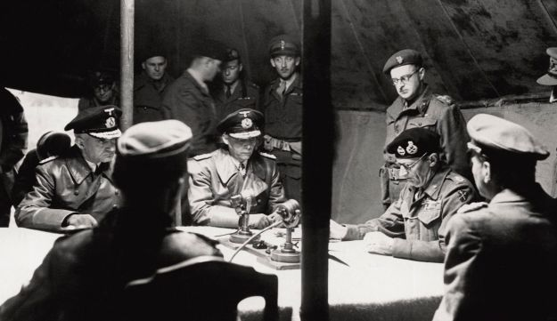 Marshal Montgomery, right, reads the surrender terms. From left, Rear Admiral Gherard von Wagner, war reporter Chester Wilmot (standing), Admiral Hans-Georg von Friedeburg, Luneburg, May 4, 1945.