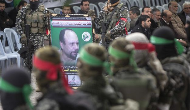 Members of the Ezzedine al-Qassam Brigades, the military wing of the Palestinian Islamist movement Hamas, hold a banner bearing a portrait of one of their leaders, Mohammed Zawahri, who was murdered in Tunisia, during a ceremony in his memory on December 18, 2016 in Gaza City.
