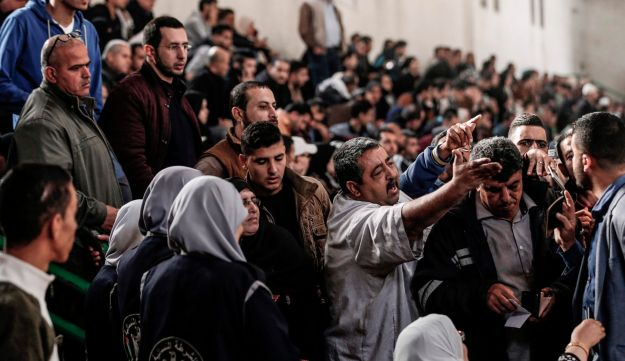 Palestinians gather in Khan Younis in the southern Gaza strip on November 18, 2017 as they await clearance to take a bus to travel through the Rafah border crossing with Egypt.