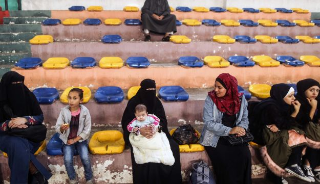 Palestinians sit in a basketball court in Khan Younis in the southern Gaza strip on November 18, 2017 as they await clearance to take a bus to travel through the Rafah border crossing with Egypt, after it opened for three days for the first time since the Palestinian reconciliation deal.