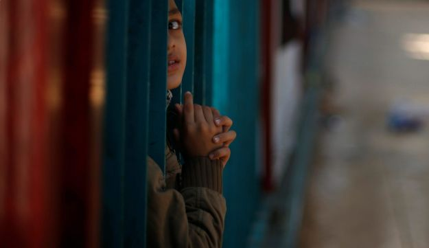 A Palestinian boy waits for a travel permit to cross into Egypt, after Rafah border crossing was opened under control of the Western-backed Palestinian Authority for the first time since 2007, in Khan Younis in the southern Gaza Strip November 19, 2017
