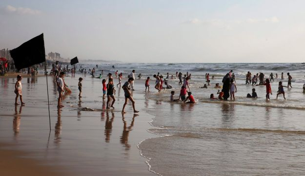 Families swim in the Mediterranean Sea on a sweltering hot day, in front of a black flag warning them not to swim in this polluted area, in Gaza City, Friday, July 7, 2017.