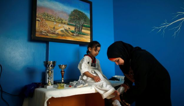Palestinian girl Roueya Al-Krunz is dressed by her mother to take part in Taekwondo training session, at their house in the central Gaza Strip October 23, 2017.