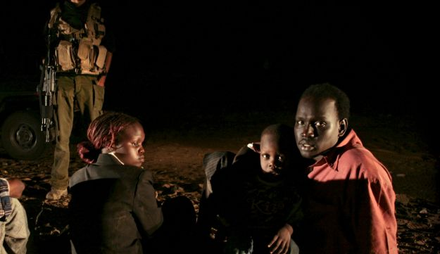 Israeli border police officers stand guard over Sudanese refugees who crossed into Israel illegally north of Nitzana, near the border with Egypt, August 20, 2007.