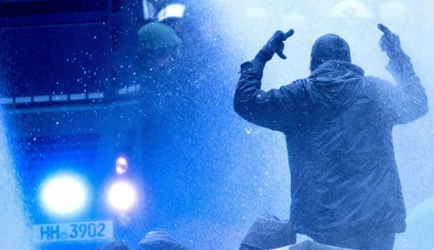 A protester flips the bird as German police uses water cannons to disperse demonstrators trying to block access to the far-right Alternative for Germany (AfD) party congress in Hanover, northern Germany. December 2, 2017