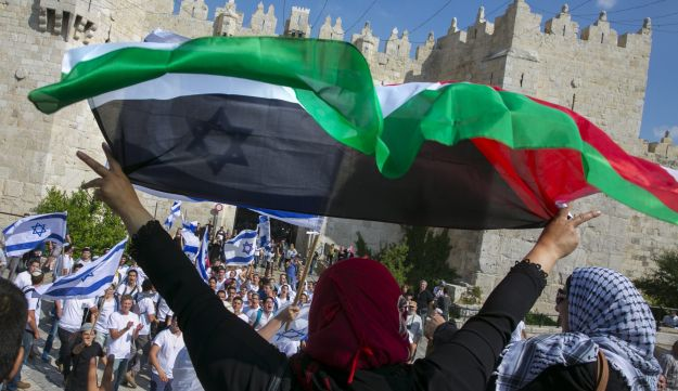 Protesters hold up Palestinian flags during the Israeli flag march held on Jerusalem Day in the city's Muslim quarter, May 24, 2017.