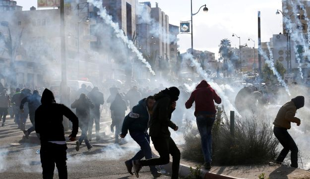 Palestinian protesters run from tear gas fired by Israeli troops during clashes at a protest against U.S. President Donald Trump's decision to recognize Jerusalem as the capital of Israel, near the Jewish settlement of Beit El, near the West Bank city of Ramallah December 7, 2017.
