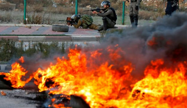 Israeli forces take position during clashes with Palestinian protesters near an Israeli checkpoint in the West Bank city of Ramallah on December 7, 2017 on December 7, 2017.