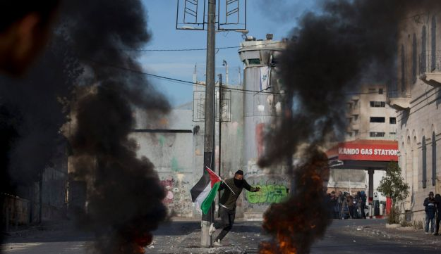 A protester carrying a Palestinian flag runs for cover during clashes with Israeli troops following protests against U.S. President Donald Trump's recognition of Jerusalem as Israel's capital. Bethlehem, Dec. 10, 2017.