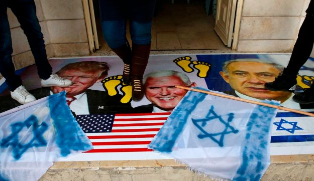 Palestinians walking on a poster bearing images of U.S. President Donald Trump, Vice President Mike Pence and Israeli Prime Minister Benjamin Netanyahu during a demonstration in the West Bank, December 13, 2017.