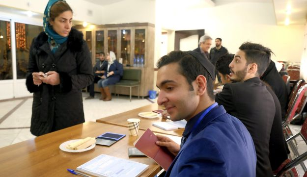 An Iranian Jew voter speaks with an election official at a synagogue used as a polling station, during elections for the parliament and Assembly of Experts, which has the power to appoint and dismiss the supreme leader, in Tehran February 26, 2016.