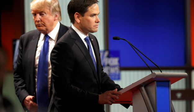 Republican U.S. presidential candidate Donald Trump walks behind rival candidate Marco Rubio.