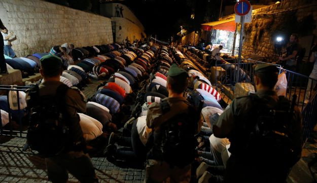 Israeli border police stand guard as Palestinians take part in evening prayers outside the Lion's Gate of Jerusalem's Old City  July 18, 2017.