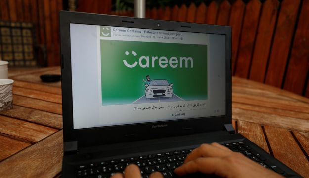 An employee shows an advertisement for ride-hailing company Careem, on a laptop in his office in the West Bank city of Ramallah July 17, 2017.