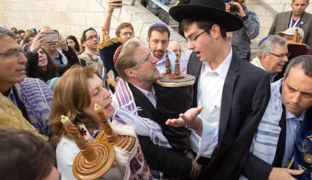 An Ultra-Orthodox Jewish man tries to prevent Anat Hoffman (C), the founder and President of the liberal Jewish religious group Women of the Wall, and members of the group, from entering the women's section of the Western Wall while carrying a Torah scroll, in the Old city of Jerusalem on November 2, 2016, during a protest by the group demanding equal prayer rights at the site.