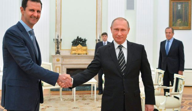 Russian President Vladimir Putin, center, shakes hand with Syrian President Bashar Assad as Russian Foreign Minister Sergey Lavrov looks on. Kremlin, Moscow. Oct. 20, 2015