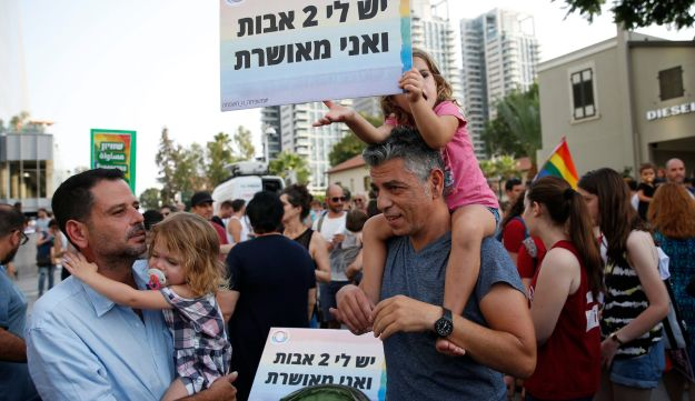 'I have two dads, and I'm happy,' reads a sign held by protestors in Tel Aviv, July 20, 2017