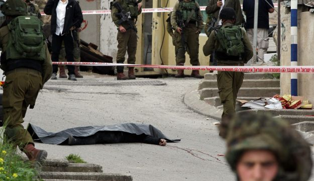 Israeli soldiers surround the body of one of the two Palestinians who were killed after attacking a soldier in Hebron, March 24, 2016.