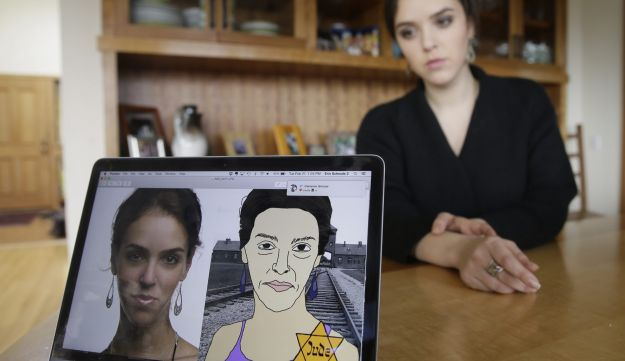 In this Feb. 21, 2017, photo, Erin Schrode poses behind a laptop displaying anti-Semitic images of herself that she received in her email and social media at her home in Mill Valley, California.