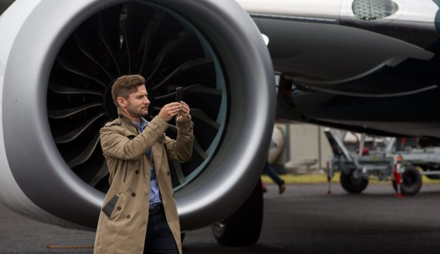 FILE PHOTO: A member of the media uses a smartphone to take a photograph of a Boeing Co. 737 Max aircraft during preparations ahead of the Farnborough International Airshow 2016 in Farnborough, U.K., on Sunday, July 10, 2016.