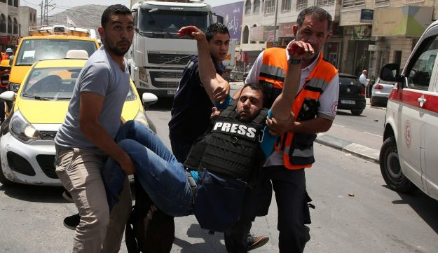 A wounded Palestinian reporter is carried by a medic and civilians in the northern West Bank on May 18, 2017 near the Hawara military checkpoint.
