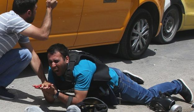 A wounded Palestinian journalist next to the body of a man killed by an Israeli settler. The Israeli was firing back at stone-throwers