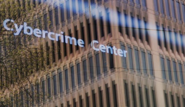 An advertisement about the Microsoft Cybercrime Center playing behind a window reflecting a nearby building at the Microsoft office in Cambridge, Massachusetts, May 2017.