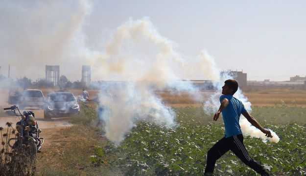 A Palestinian protester hurls a teargas canister back at Israeli soldiers during clashes following a protest against the blockade on Gaza, near the border fence east of Gaza City on May 19, 2017.