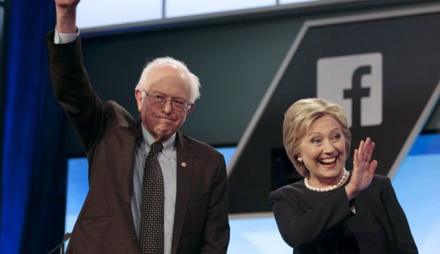 Presidential candidates Bernie Sanders and Hillary Clinton wave before the start of the Democratic debate in Florida, March 9, 2016.