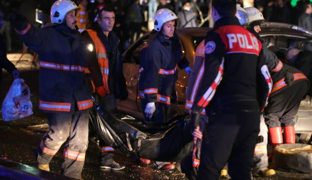 A police officer looks on as a body bag is carried at the scene of a blast in Ankara on March 13, 2016.