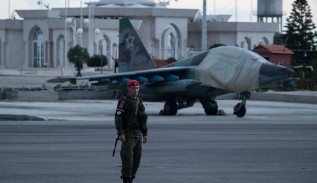 A Russian soldier guards a Russian attack jet parked at Hemeimeem air base in Syria, March 4, 2016.