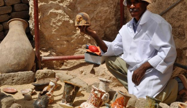 A member of an Egyptian archaeological team shows artifacts discovered in a 3,500-year-old tomb in the Draa Abul Nagaa necropolis, near the southern city of Luxor, on April 18, 2017.