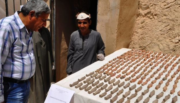 A member (R) of an Egyptian archaeological team stands near artifacts discovered in a 3,500-year-old tomb in the Draa Abul Nagaa necropolis, near the southern city of Luxor, on April 18, 2017.