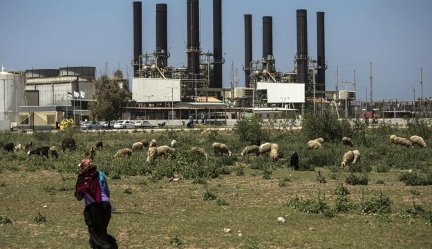A Palestinian woman walks past a power plant in Gaza City on April 16, 2017.