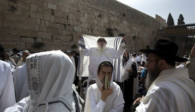 Israeli ultra-Orthodox Jewish men participate in the Cohanim Priestly caste blessing during the Jewish holiday of Passover, in front of the Western Wall, the holiest site where Jews can pray in Jerusalem's old city, Monday, April 25, 2016.