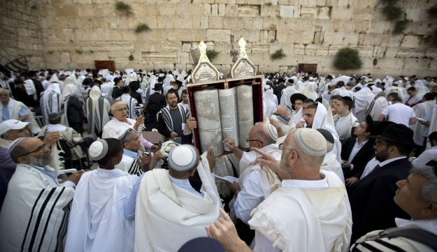 Israelis hold a Torah scroll prior to the Cohanim Priestly caste blessing during the Jewish holiday of Passover, in front of the Western Wall, the holiest site where Jews can pray in Jerusalem's old city, Monday, April 25, 2016.