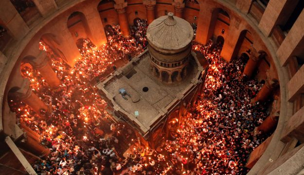 "Christian Orthodox worshippers hold up candles lit from the ""Holy Fire"" as thousands gather in the Church of the Holy Sepulchre in Jerusalem's Old City, on April 30, 2016."