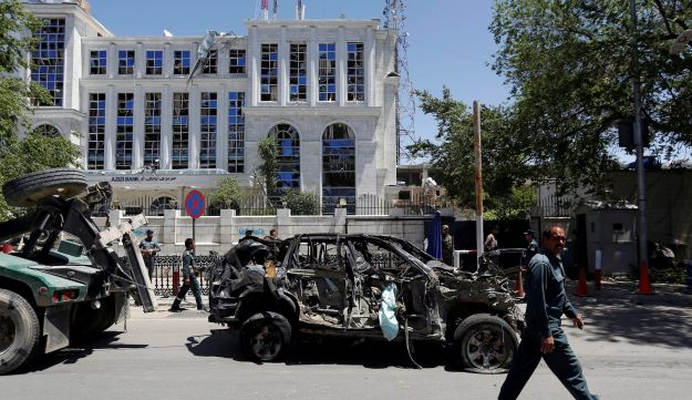 An Afghan policeman past walked next to a damaged vehicle after a blast in Kabul, Afghanistan, May 31, 2017.