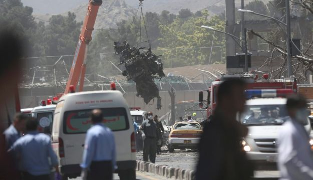 Security forces inspect the site of a car bombing and remove destroyed vehicles, in Kabul, Afghanistan, May 31, 2017.