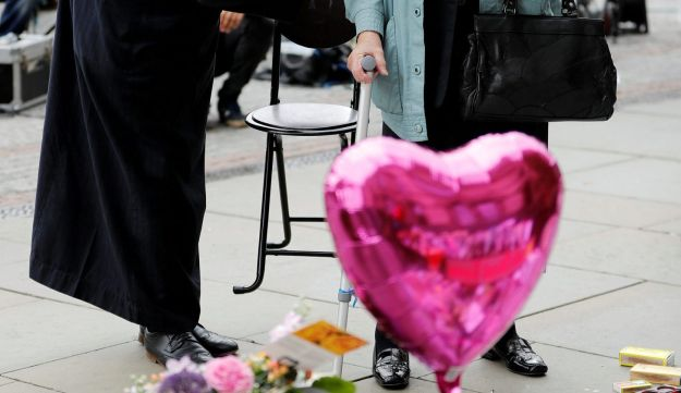 REFILE - CORRECTING LOCATION A Muslim man named Sadiq Patel comforts a Jewish woman named Renee Rachel Black next to floral tributes in Albert Square in Manchester, Britain May 24, 2017. REUTERS/Darren Staples