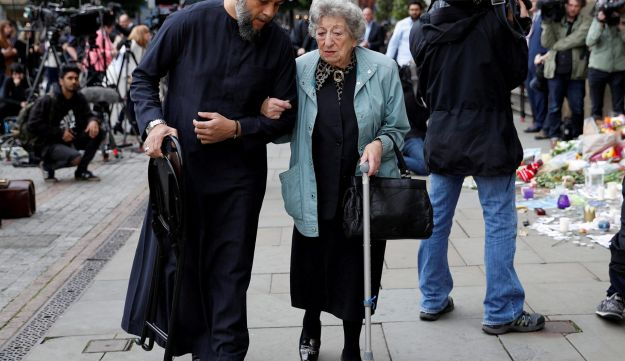REFILE - CORRECTING LOCATION A Muslim man named Sadiq Patel and a Jewish woman named Renee Rachel Black walk by floral tributes in Albert Square in Manchester, Britain May 24, 2017. REUTERS/Darren Staples