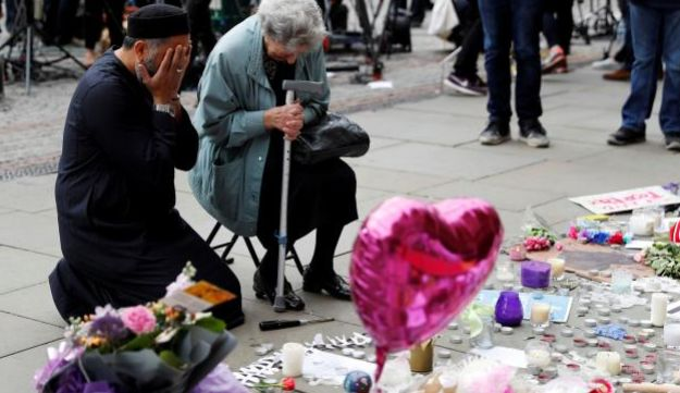 A Jewish woman named Renee Rachel Black and a Muslim man named Sadiq Patel react next to floral tributes in Albert Square in Manchester, Britain May 24, 2017.