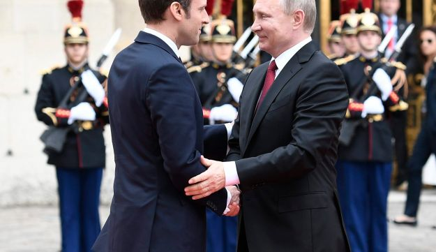 French President Emmanuel Macron shakes hands with his Russian counterpart Vladimir Putin as they meet for talks at the Palace of Versailles near Paris, May 29, 2017.