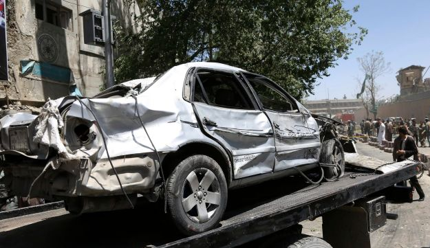 Security forces carry the wreckage of car near the site of a suicide attack where German Embassy is located in Kabul, Afghanistan, May 31, 2017.